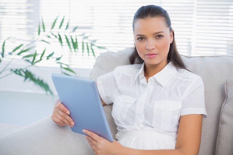 Mulher bonito séria que guardara a tabuleta que senta-se no sofá confortável imagem de stock