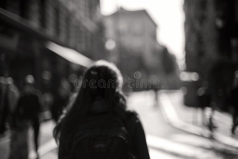 Mulher borrada do passeio de trás através da cidade borrada fotografia de stock royalty free