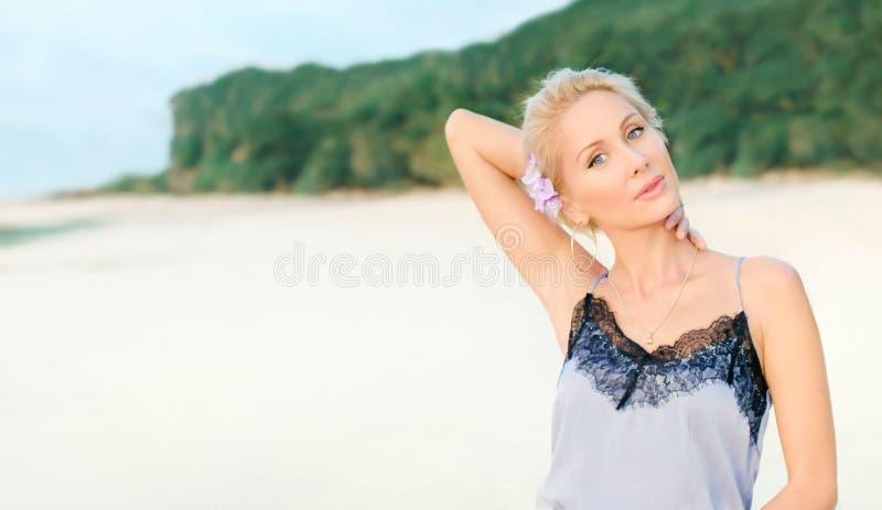 Mulher branca bonita com cabelo curto em uma costa da praia no vestido elegante com laço preto Suporte da menina perto do oceano  foto de stock