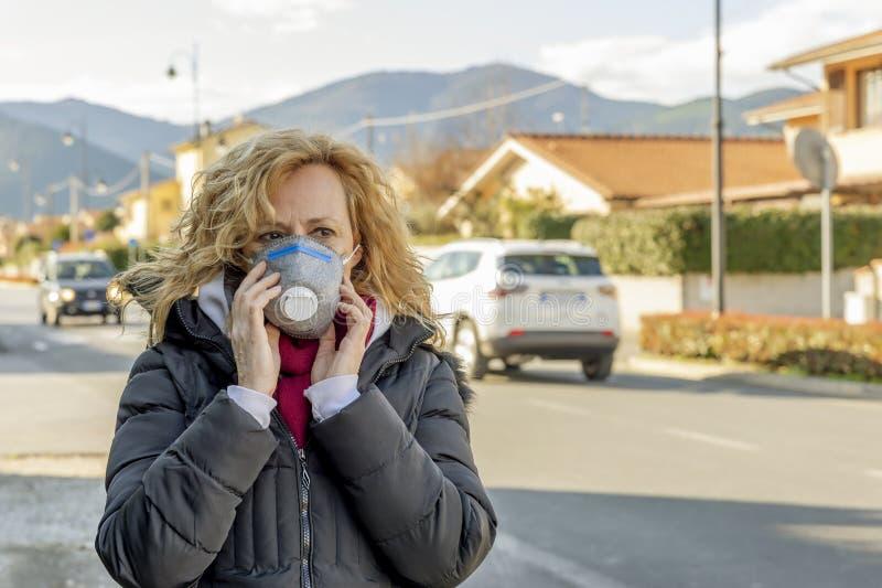 Mulher branca caminha pela rua com a máscara protetora nos tempos do coronavírus 'Covid - 19', que está afetando muita gente fotografia de stock