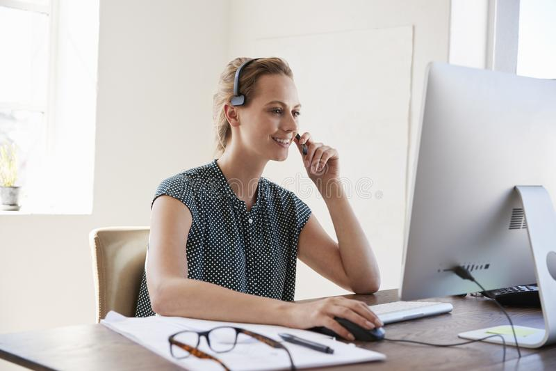 Mulher branca de sorriso no computador em uns auriculares vestindo do escritório imagens de stock