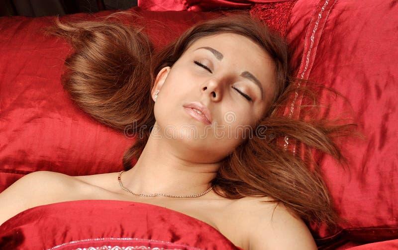 A mulher branca dorme no linho vermelho foto de stock