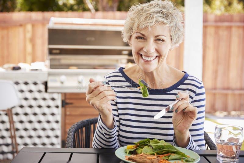Mulher branca superior que come o almoço em uma tabela em seu jardim fotos de stock