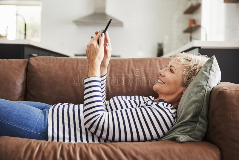 Mulher branca superior que encontra-se no sofá em casa que usa o smartphone fotos de stock royalty free