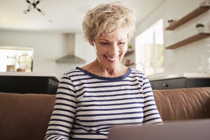 Mulher branca superior que usa o laptop em casa, fim acima fotografia de stock