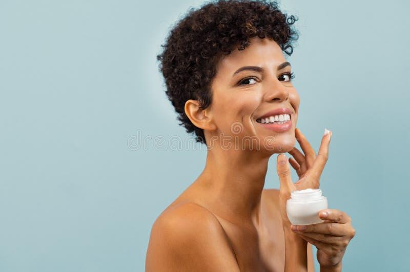 Mulher brasileira nova que aplica o creme hidratante imagens de stock royalty free