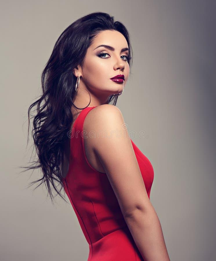 Mulher brilhante bonita da composição com penteado encaracolado preto longo no vestido vermelho, batom de Borgonha com olhar do c imagens de stock