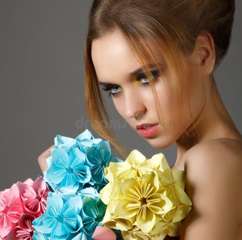 A mulher brilhante bonita que guardara o ramalhete do origâmi de papel floresce fotos de stock royalty free