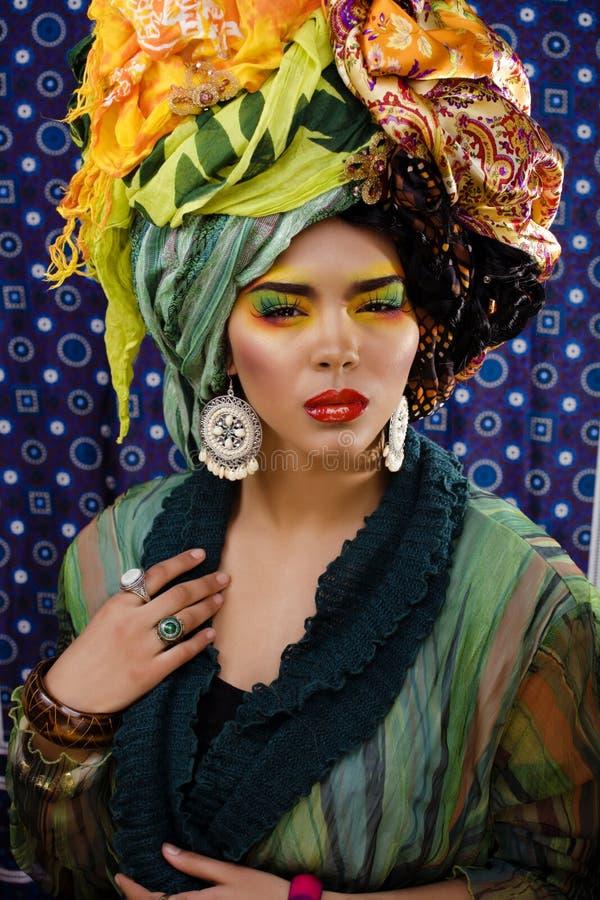 A mulher brilhante da beleza com criativo compõe, muitos xailes na cabeça imagem de stock royalty free