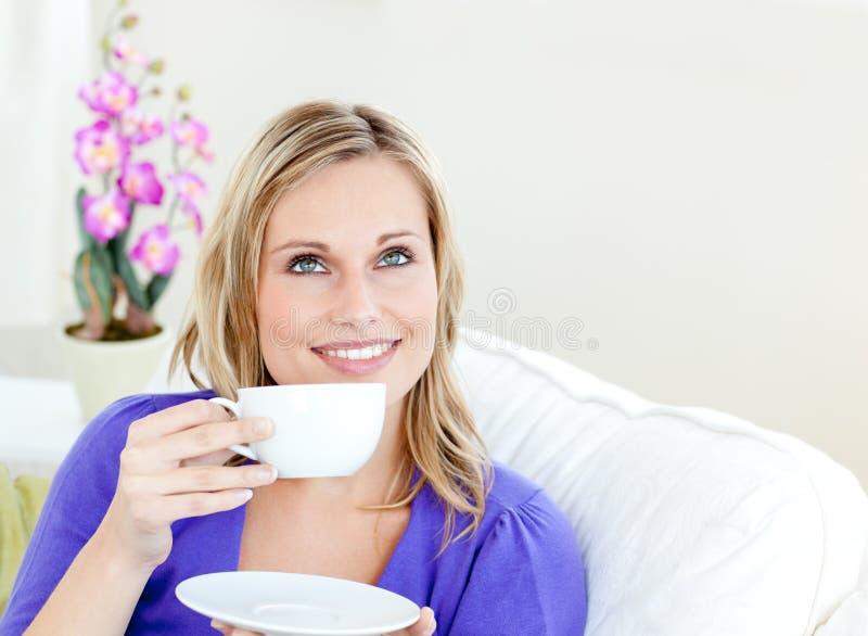 Mulher brilhante que aprecia seu café em um sofá em casa fotos de stock