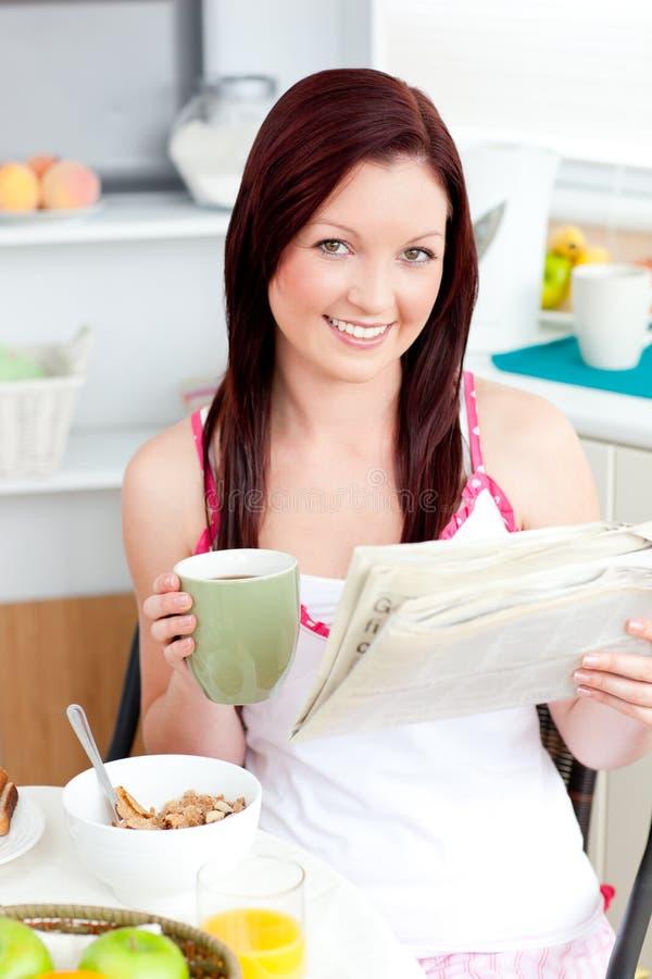 Mulher brilhante que come cereais e que lê o jornal imagem de stock royalty free