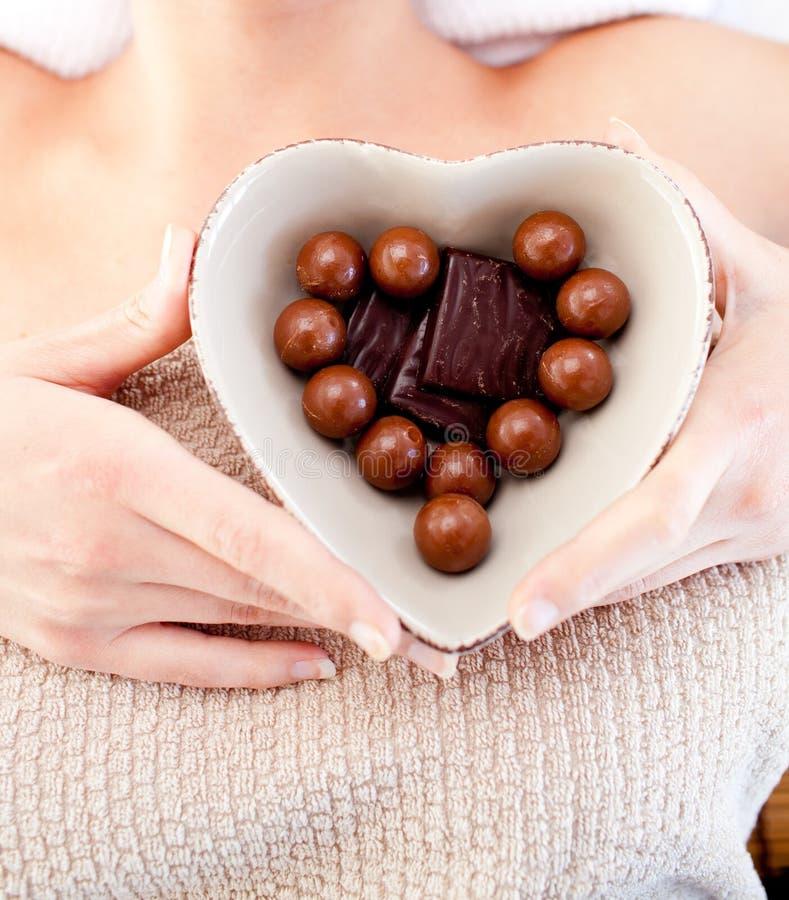 Mulher brilhante que prende uma bacia com chocolates imagem de stock