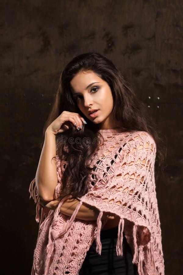 Mulher bronzeada bonita com o cabelo luxúria longo que levanta no sweate cor-de-rosa foto de stock royalty free