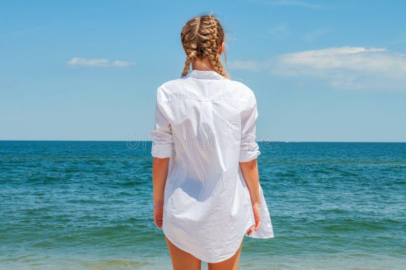 Mulher bronzeada bonita na camisa branca que olha o oceano, na praia imagens de stock royalty free