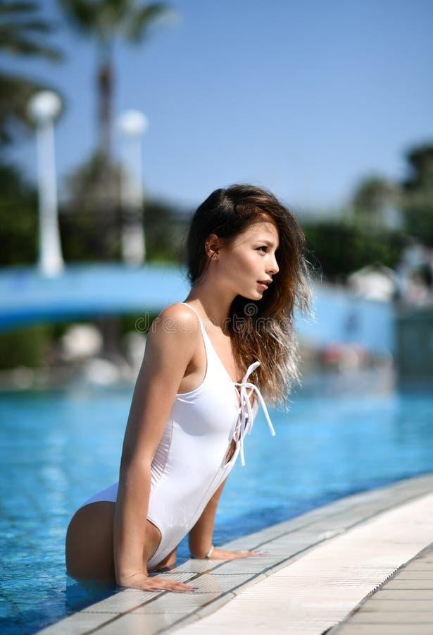 Mulher bronzeada bonita no roupa de banho azul que relaxa no hotel de spa resort da piscina no dia de verão quente imagens de stock