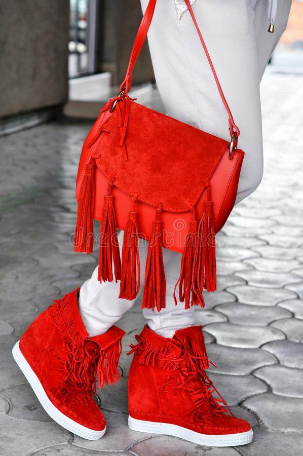 Mulher bronzeada magro que veste os saltos altos vermelhos com borlas e o saco vermelho com franja Fôrma da rua Olhar da rua da f imagens de stock royalty free