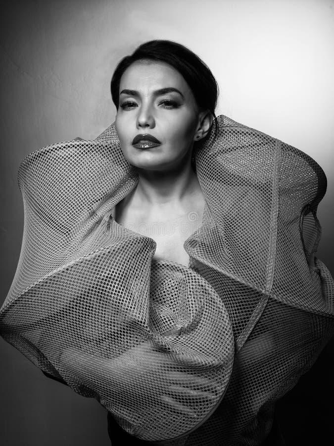 Mulher bronzeada magro 'sexy' nova em uma gaiola de pesca que levanta contra o fundo cinzento fotografia de stock