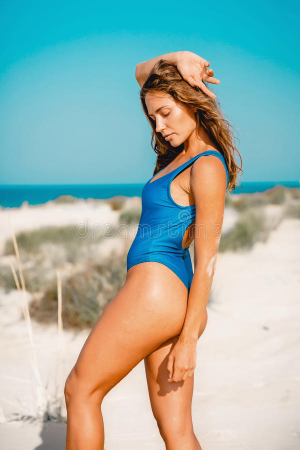 Mulher bronzeada no roupa de banho azul que levanta na praia da areia Corpo da mulher do verão fotografia de stock royalty free