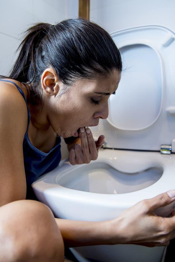 Mulher bulímica que sente os dedos culpados doentes na boca que vomita e que joga acima no toalete do WC fotografia de stock royalty free