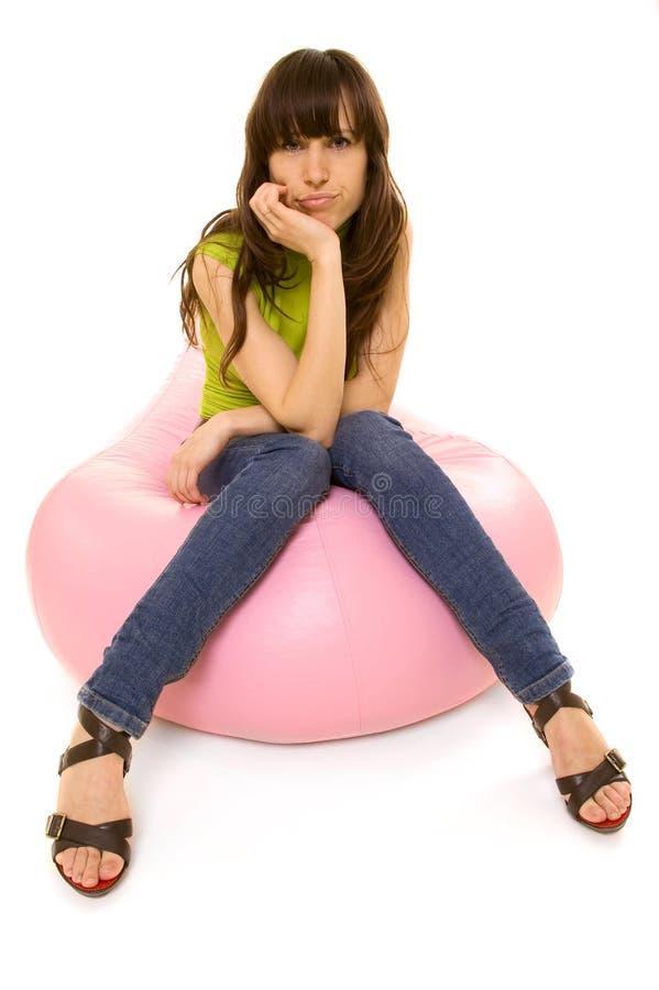 Mulher céptica que senta-se na cadeira imagens de stock royalty free