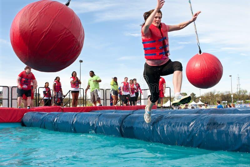 A mulher cai na água na raça louca do curso de obstáculo imagens de stock