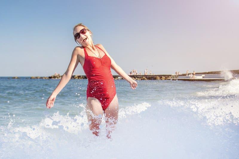 Mulher caicasian bonita nova no roupa de banho vermelho que tem o divertimento que espirra na onda na gravidez feliz da costa do  fotos de stock