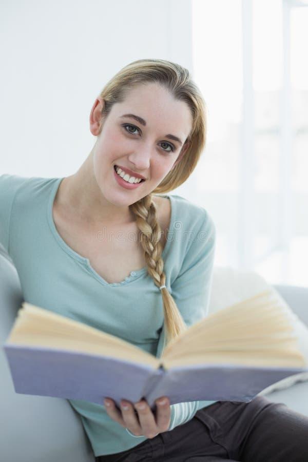Mulher calma bonito que relaxa lendo um livro que senta-se na sala de visitas foto de stock