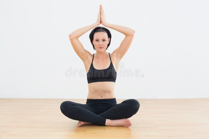 Mulher calma na pose dos lótus que medita no estúdio da aptidão foto de stock