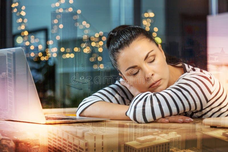 Mulher calma que dorme ao ser em casa e ao descansar na tabela fotografia de stock