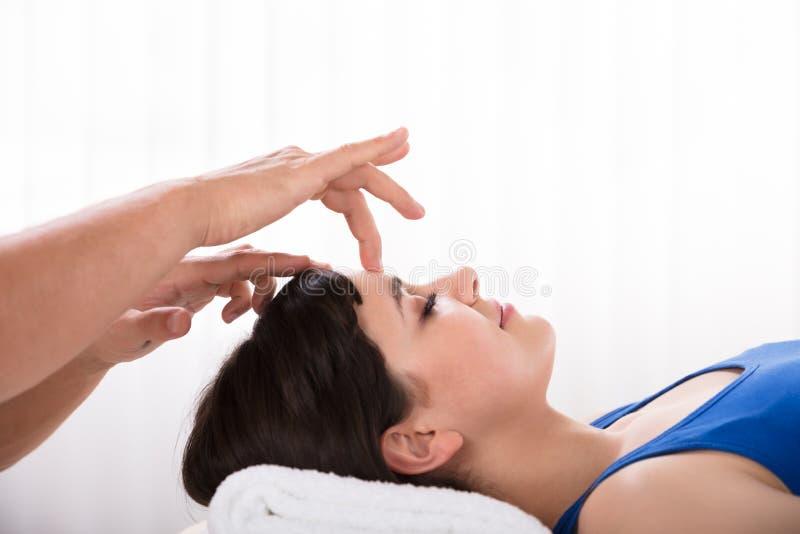 Mulher calma que recebe o tratamento do reiki fotografia de stock