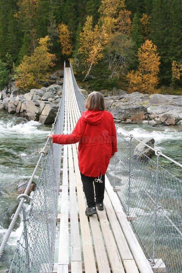 Mulher caminhando sobre uma ponte de suspensão imagem de stock royalty free