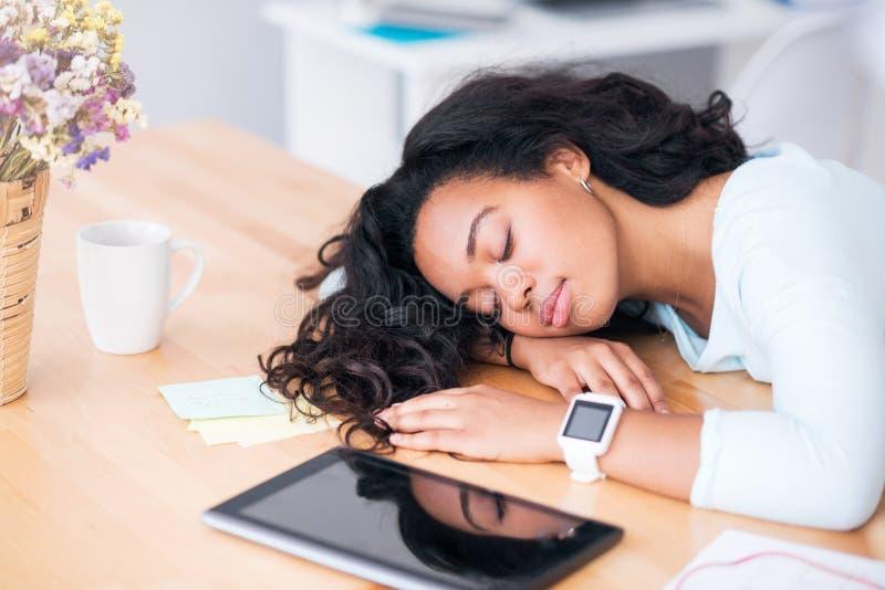 Mulher cansado agradável que dorme na tabela fotos de stock royalty free