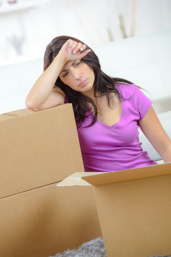 Mulher cansado bonita em caixas moventes próximas do assoalho imagens de stock