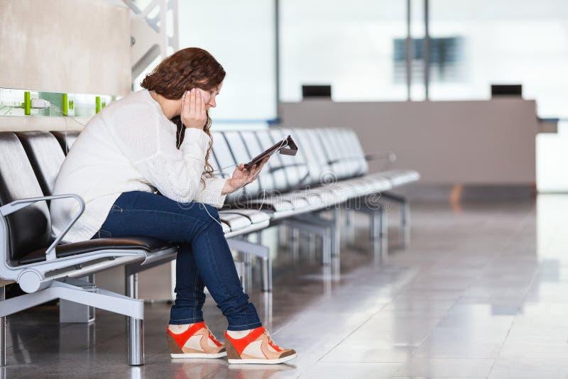Mulher cansado com os dispositivos que sentam-se na sala de estar do aeroporto imagem de stock