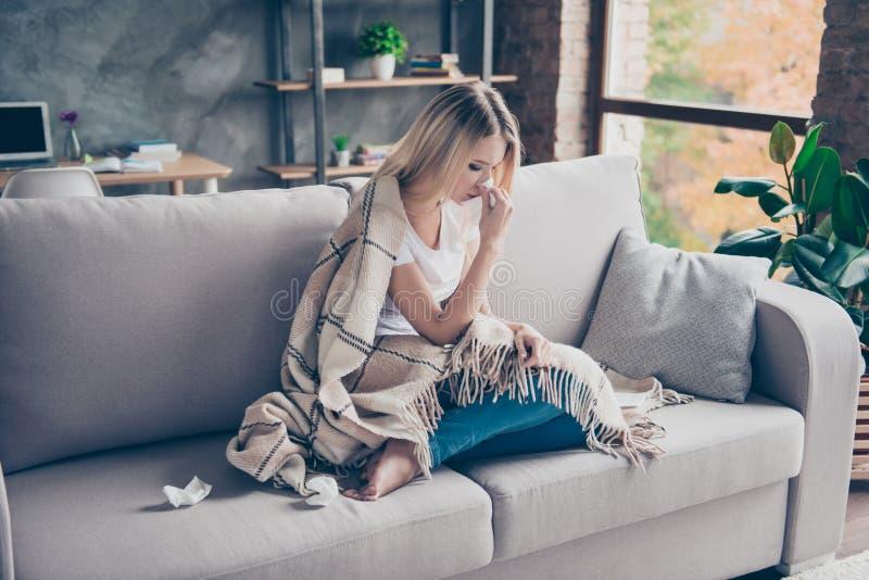 A mulher cansado da virada infeliz está sentando-se em um sofá em casa Pode ` fotografia de stock