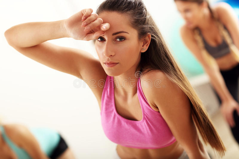 Mulher cansado e suado mas satisfeita após o exercício no gym imagem de stock