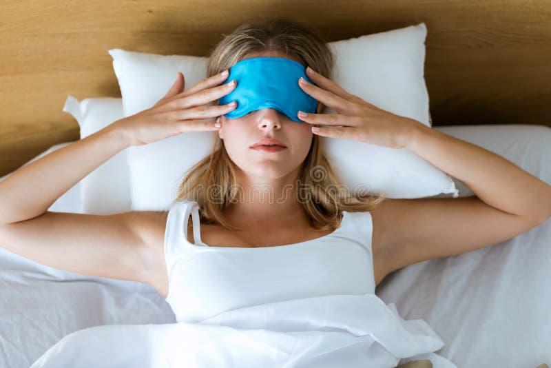 Mulher cansado nova bonita que tenta dormir com a máscara do sono que descansa na cama no quarto em casa imagens de stock royalty free