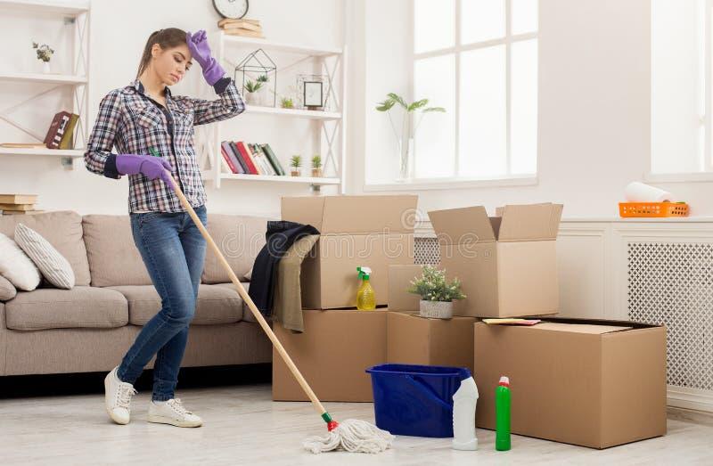 Mulher cansado nova que limpa a casa nova com o espanador foto de stock