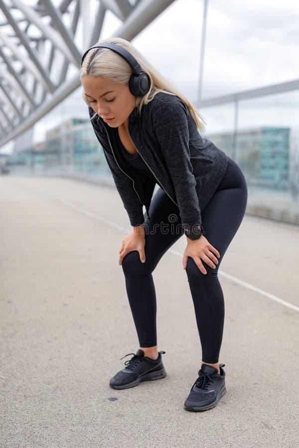 Mulher cansado que descansa com mãos em joelhos após ter corrido o exercício fotografia de stock royalty free