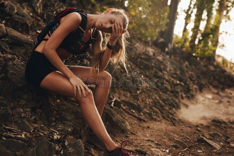 Mulher cansado que descansa pela fuga de montanha após uma corrida imagens de stock royalty free