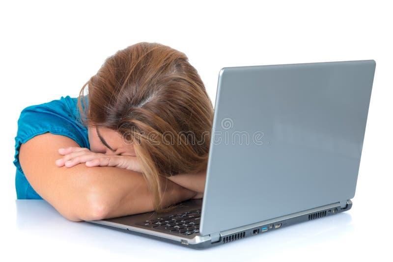 Mulher cansado que dorme sobre seu computador fotos de stock