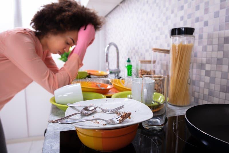 Mulher cansado que inclina-se perto do dissipador com utens?lios sujos imagens de stock