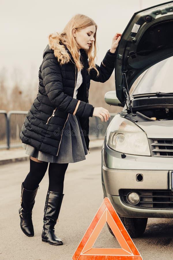 Mulher, carro quebrado e auto triângulo na estrada foto de stock royalty free