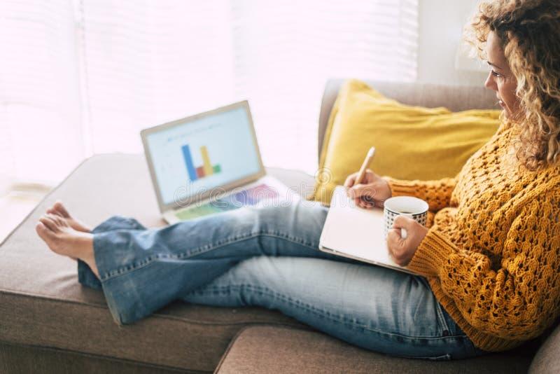 Mulher caucasiana adulta relaxada no trabalho em casa com computador portátil pessoal e notebook - economia e alternativa de negó