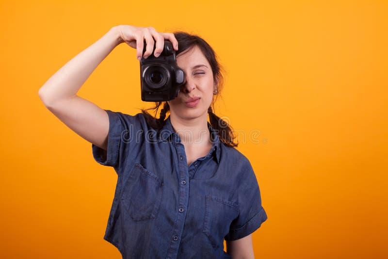 Mulher caucasiano atrativa com a câmera da foto que focaliza no estúdio sobre o fundo amarelo imagem de stock royalty free