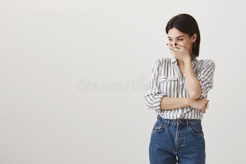 Mulher caucasiano atrativa com cabelo escuro curto na roupa ocasional à moda que zomba e que ri, cobrindo a boca, tentando imagem de stock royalty free