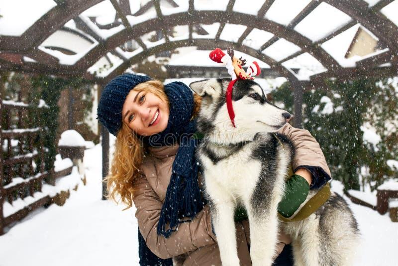 A mulher caucasiano autêntica atrativa abraça o cão engraçado do malamute que veste chifres do Natal de Santa os caros Fêmea de s fotografia de stock