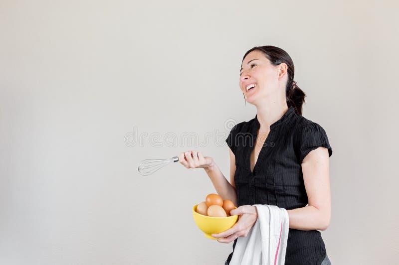 Mulher caucasiano bonita com a camisa preta que guarda um eggbeater e uma bacia amarela completamente de ovos da galinha foto de stock