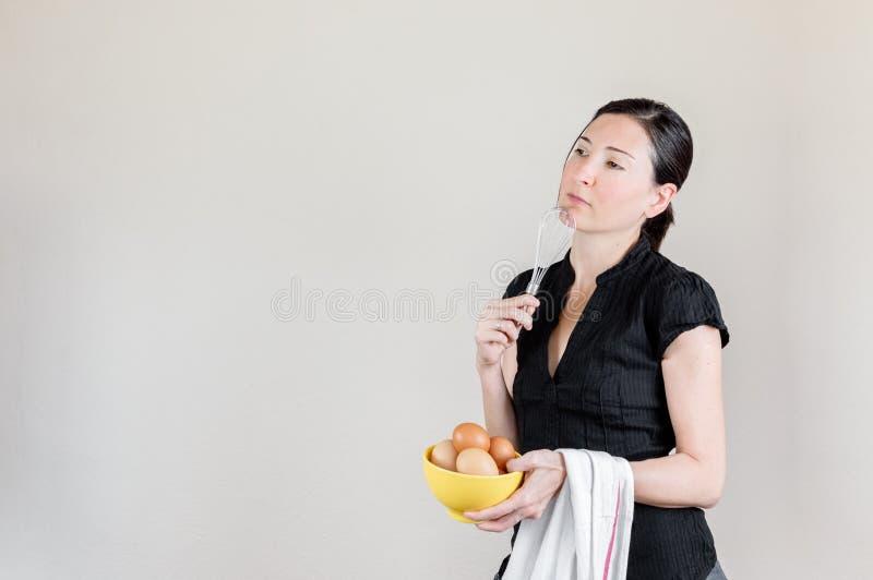 Mulher caucasiano bonita com a camisa preta que guarda um eggbeater e uma bacia amarela completamente de ovos da galinha imagem de stock royalty free