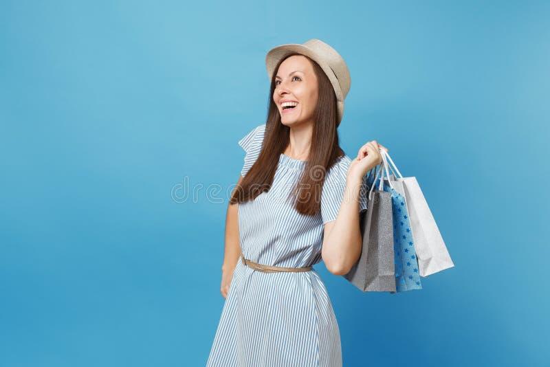 Mulher caucasiano bonita de sorriso elegante do retrato no vestido do verão, chapéu de palha que guarda sacos dos pacotes com com fotos de stock